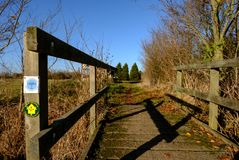 View of a wooden framed public footbridge seen at the side of a circular walk in a rural location. The emblem on the left is part of a Pathfinder circular walk Stock Photo