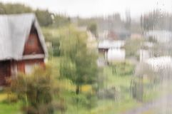Wet window on a rainy day. View of the wooden house from the wet window on a rainy day, blur backgrounds, unfocused picture royalty free stock image
