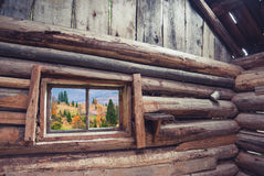 View from wooden house. View from window of rustic wooden house to Carpathian mountain village. Ethnic cottage Stock Image