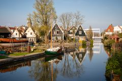 View of wooden houses, shipyard and boats along a canal in the historic town of Edam, Netherlands stock image