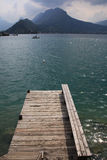 View from a wooden jetty over Lake Annecy. Wide angle view of a pontoon on a lake with mountains in the horizon, lake Annecy, France royalty free stock image