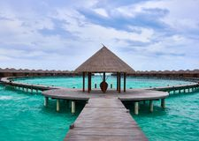 View of circular wooden path leading to water villas located on turquoise sea of the Coco Bodu Hithi resort in Maldives. stock photography