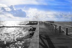 Sea view in black and white on a colored horizon. View of a wooden pier in black and white on a blue horizon Stock Image