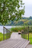 A wooden walking path with handrails in park on the river coast. View on a wooden walking path with handrails in park on the river coast stock photography