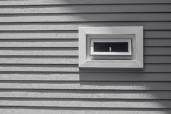 View of wooden window on gray wall of wooden house at countryside. Stock Image
