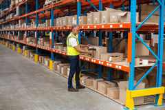 View of worker is checking cardboard boxes. In a warehouse Stock Image