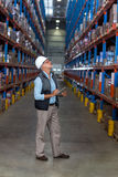 View of worker is looking shelves and holding a clipboard Royalty Free Stock Images