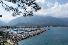 View of yacht marina and mountains in Kemer Antalya. KEMER, TURKEY - APRIL 25 View of yacht marina and mountains with turqoise sea and cloudy sky IN 2016 Royalty Free Stock Images