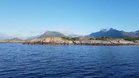 View from yacht sailing along coast of Lofoten Islands with pyramids for codfish drying. View from yacht sailing along green coast of Lofoten Islands with stock video