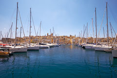 The view of yachts moored in harbor in Dockyard creek with Senglea peninsular on background. Malta. The view of yachts moored in the harbor in Dockyard creek stock photo