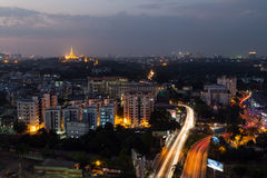 View of Yangon from above at dusk. View of Yangon, Myanmar, from above in the evening. Lit Shwedagon Pagoda is in the distant Stock Photos