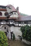 Misty day in the castle. View into a yard of a Bran castle with red roofs and white buildings and trees stock image