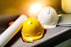 View of yellow safety helmet hat in the project at construction site building on concrete floor on city with sunlight. helmet royalty free stock image