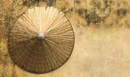 Yellow shabby wall with Vietnamese hat on it Stock Images