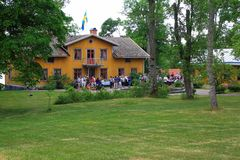 View of a yellow village house with swedish flag on the roof. Many guests coming for outdoor party on a summer day. Beautiful swedish nature royalty free stock photography