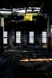 Load Capacity Sign with Collapsing Ceiling & Floor - Abandoned Glass Factory. A view of a yellow weight limit sign above collapsing wood floors and among four Royalty Free Stock Photo
