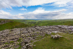 View of the Yorkshire dales over the rocky Malham cove. With a cloudy sky Stock Image