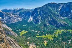 View of the Yosemite Valley with Visitor Center and the Sierra Nevada mountain range from the trail to Upper Yosemite royalty free stock photos