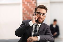 View of a Young attractive business man using smartphone. Portrait of handsome business man using cell phone Royalty Free Stock Photo
