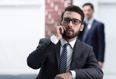 View of a Young attractive business man using smartphone. Portrait of handsome business men using cell phone Royalty Free Stock Photo