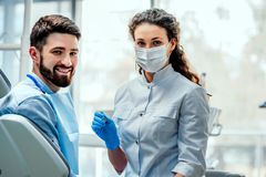 View of a young attractive dentist explaning his work to a patient stock images