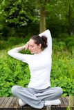 Young attractive woman practising yoga in a park. View of a Young attractive woman practising yoga in a park Stock Photography