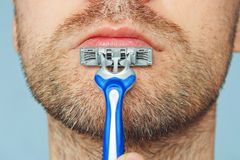 View of a young bearded man with a brutal razor. face on the blue background. big rough hairy bristles on the skin, close up. View of a young bearded man with a Royalty Free Stock Images