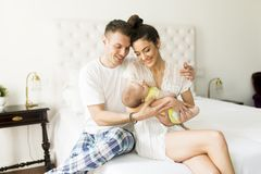 Young couple on the bed with baby girl. View at young couple on the bed with baby girl Stock Photo