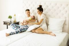 Young couple on the bed with baby girl Royalty Free Stock Photo