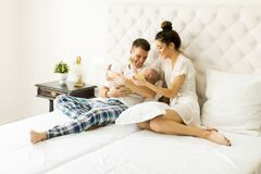 Young couple on the bed with baby girl Stock Image