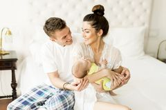 Young couple on the bed with baby girl. View at young couple on the bed with baby girl Royalty Free Stock Photo