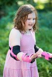 Young girl outside learning to riding on roller skates on driveway wearing protective elbow, wrist and knee pads. View of Young girl outside learning to riding Royalty Free Stock Photos