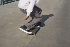Young male skates low on a pier stock images