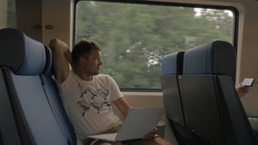 View of young man sitting in the train and using laptop against window during trip, Netherlands stock video footage