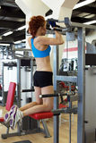 View of young redhead girl exercising on simulator Royalty Free Stock Photo