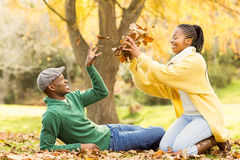 View of a young smiling couple in leaves Royalty Free Stock Images