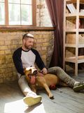 View of young sportive man having fun with dog at home. Dogman and staffordshire terrier sitting on floor at home interior Royalty Free Stock Image