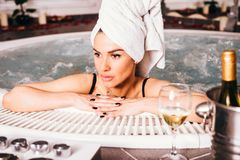 Young woman relaxing in the hot tub. View at Young woman relaxing in the hot tub royalty free stock photography