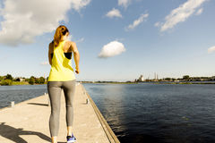 View of young woman running on dock by river in morning. Health conscious concept royalty free stock photos