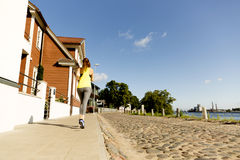 View of young woman running on sidewalk in morning. Health conscious concept royalty free stock image