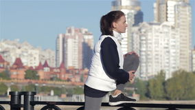 View of a young woman stretching on foot bridge stock footage