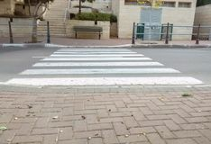 Zebra cross between two tiled sidewalks, with stairs leading up Stock Image