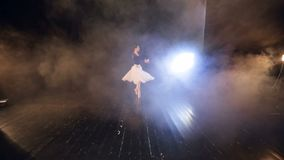 A view from the seats to a stage with a ballerina.