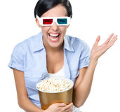 Viewer watching 3D cinema with bowl of popcorn royalty free stock image