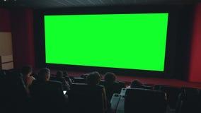 Viewers enjoying movie on big green screen copyspace in dark cinema