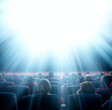 Viewers look at shining light in the cinema Royalty Free Stock Image
