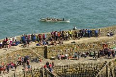 Viewers on seawall and  rowing boat at Clovelly, Devon Stock Photo