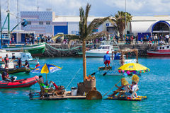Viewers watch as participants take to water in yearly. Participants take to water in a variety of unlikely crafts in the port for the yearly Regata de Achipencos royalty free stock images