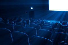 Viewers watch a 3D movie, blue toning. Viewers watch a 3D motion picture in special glasses, blue toning stock photography