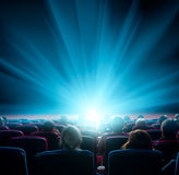 Viewers watch shining light in the cinema. Viewers watch shining light at the cinema, long exposure, blue glow Stock Photo